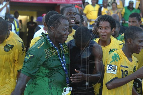 Adrian Frater photoJamaica's coach Wendell Downswell (second left) is soaking wet after being doused with the contents of the drinks igloo during the celebrations following the young Reggae Boyz 2-1 win against Honduras at the Montego Bay Sports Complex in Catherine Hall, Montego Bay, yesterday.