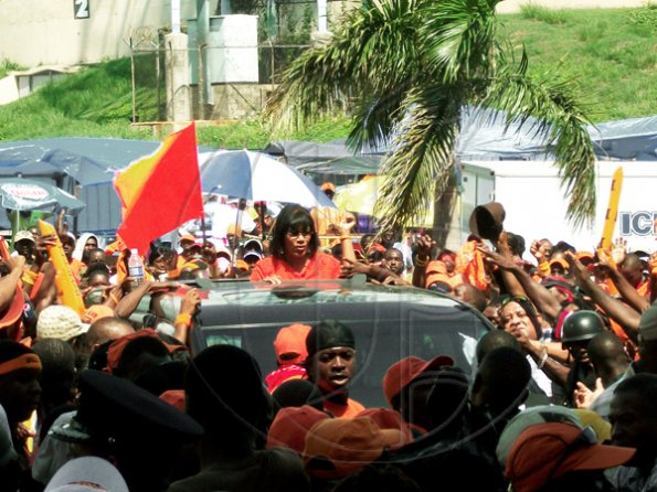 PNP President Portia Simpson Miller approaches the entrance to the National Arena flanked by thousands of party supporters.