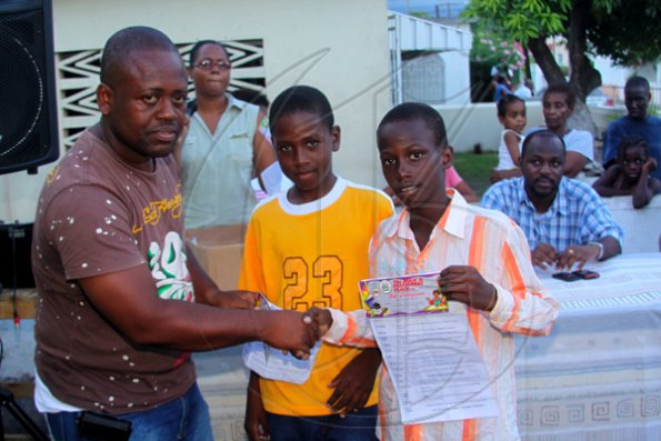 Anthony Minott/Freelance Photographer Keith Blake (left), Councillor for the Independence City Division hands over book vouchers to Jamar Samuels (right), and Ronaldo Able during a back-to-school project instigated by Councillor for the Independence City Division, Keith Blake.