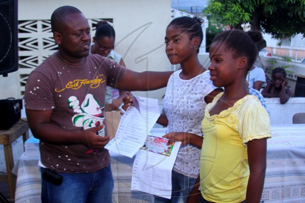 Anthony Minott/Freelance Photographer Keith Blake (left), councillor for the Independence City Division hands over book vouchers to two students from his division during a back-to-school project instigated by Councillor Blake recently.