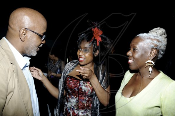 Winston Sill / Freelance Photographer Eumirel Stjeward makes a point to Pulse head honcho KIngsley Cooper while his sister Donette-Ann looks on.    Caribbean Fashion Week (CFW) Opening Reception, held at Spanish Court Hotel, New Kingston on Thursday night June 9, 2011.