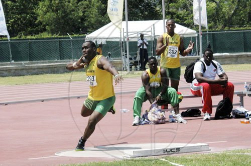 Adrian Frater photo Jamaica's Ashinia Miller (left) prepares to launch the shot put, during the Under-20 boys' competition at the CARIFTA Games, at the Montego Bay Sports Complex yesterday. Miller established a new meet record for the event.   is full flight on his way to breaking the CARIFTA Games Under-20 shott putt record in Montego Bay yesterday.