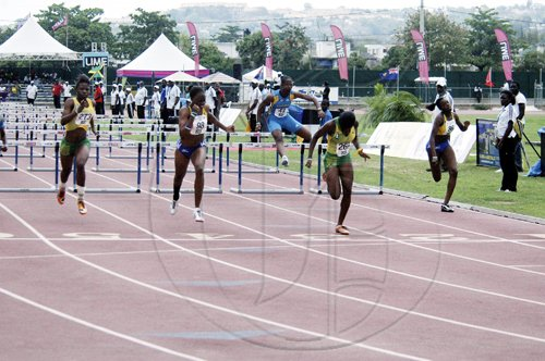 Adrian Frater photo Jamaica's Yanique Thompson (second right) crosses the finish line to win gold in the Under-17 girls' 100m hurdles final during the LIME CARIFTA Games, at the Montego Bay Sports Complex yesterday.