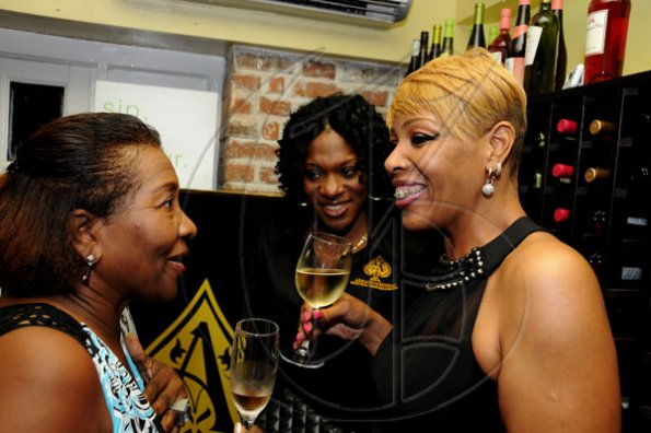Winston Sill / Freelance Photographer Marilyn Bennett (left), Kellisha Lawrence (centre) and Sharon Graham enjoying some wine and good company.  ******************************************************  Launch of Armand De Brignac Champagne, held at Bin 26, Devon House, Hope Road on Tuesday night July 5, 2011.