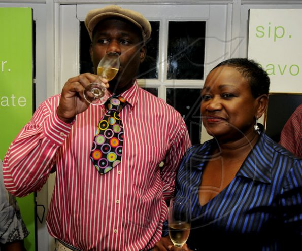 Winston Sill / Freelance Photographer Colin Hylton (left) took a break from the kitchen while Minna Israel got a break from the bank and they both got to relax and sip on fine wine at the launch of Armand de Brignac, the world number one champagne held at Bin 26 Wine Bar, Devon House on July 5.      Launch of Armand De Brignac Champagne, held at Bin 26, Devon House, Hope Road on Tuesday night July 5, 2011.