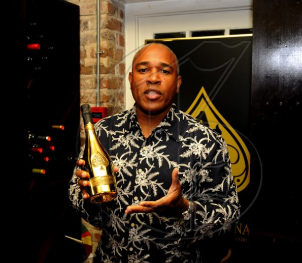 Winston Sill / Freelance Photographer Christopher Reckord showing off a bottle of the Armand De Brignac.  ******************************************************* Launch of Armand De Brignac Champagne, held at Bin 26, Devon House, Hope Road on Tuesday night July 5, 2011.
