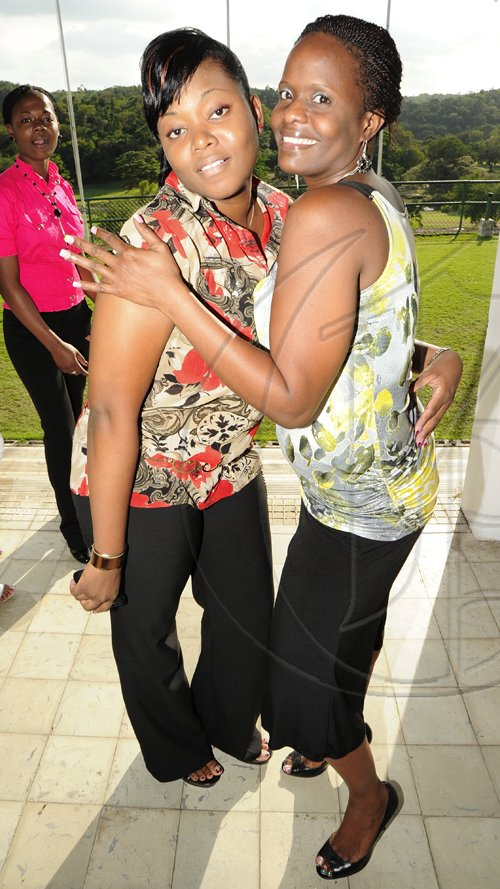 Rudolph Brown/Photographer Camise Williams (left) and Rosa Lee Kelly-Brown show that they can pose.  ***************************************************************** at the St. Catherine Co-operative Credit Union Christmas awards luncheon at Caymanas Golf and Country Club on Wednesday, December 22-2010