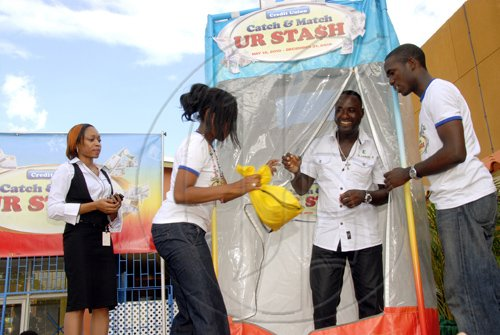 Mr. Garnett Dean, exit the money machine. He is assisted by JCCUL's  Marketing representatives , Laurel Clayton-Hall (second left) and Jason Broomfield ( right). Ms Nichelle Mighten, PricewaterhouseCoopers.( right)