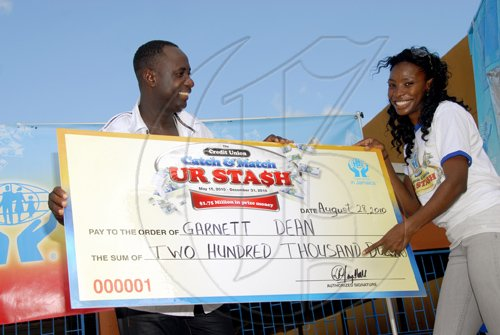Mr. Dean smiles after receving his cheque for $200,000 from Olympic 400m hurdles champion , Melaine Walker.