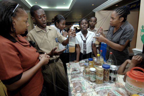 Ian Allen/Staff Photographer Marcia Clarke (right), teacher at Linstead Primary shows some of the different samples of syrups the school had on display during the Jamaica Public Service Science and Technology Expo 2009 at the Knutsford Court Hotel in Kingston yesterday. Linstead Primary took home sectional prizes.