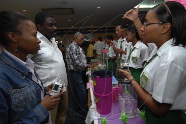 Ian Allen/Staff Photographer Khrystal Binns right , of St.Mary High School explains how they do Lemon Grass extraction during the Jamaica Public Service Science and technology EXPO 2009 at the knutsford Court Hotel in Kingston on thursday.
