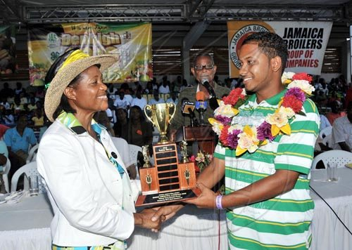 Contributed                                                                              Her Excellency, the Most Hon. Lady Allen, presents the 2010 Junior Champion Farmer Trophy to 22-year old Rahim Baccas yesterday (August 1), at the Denbigh Agri- Industrial Show in May Pen, Clarendon. Baccas, who is a livestock and ground provision farmer, was winning the trophy for the second time, having captured the title in 2009.