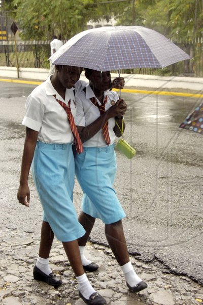 Norman Grindley/Chief Photographer Students heading home after their orientation at Wolmer's Girls' School in Kingston yesterday. They were seen heading up Marescaux Road after a shower of rain.