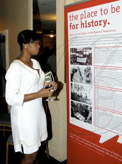 Winston Sill / Freelance Photographer Annalise Freckleton takes in some of the German history that was on display.  ********************************************************************************** at the German Day of Unity reception, held at the Jamaica Pegasus Hotel, New Kingston on Monday night October 4, 2010.