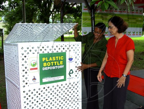 "Winston Sill / Freelance Photographer Scotiabank Group hand over ""Receptacles to the University of the West Indies (UWI) Plastic Bottle Recycling Project, and Unveiling of Scotiabank Goes Green"",  held at the UWI Centre for Environmental Management, Mona Campus on Tuesday May 18, 2010.  Here are Heather Goldson (left), Senior Vice President, Marketing, Public and Corporate Affairs, Scotiabank hand over one of the Receptacles to Prof Elizabeth Thomas Hope (right), Director, Centre for Environmental Management, UWI."