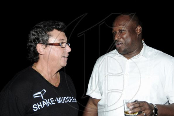 Winston Sill / Freelance Photographer Anthony Bell (left); and Andrew Pryce enjoy their drinks.   *****************************************************************.Appleton Estate Jamaica Rum International Bartender Showcase 2010, held at in the Sunken Garden at Hope Gardens, Old Hope Road on Friday night October 22, 2010. Here are Anthony Bell (left); and Andrew Pryce (right).
