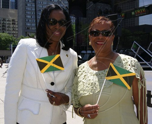Contributed                                                                                                                                                                                                                                                          Jamaica's High Commissioner to Canada, Her Excellency Sheila Sealy Monteith (left) and Regional Director for the Jamaica Tourist Board (JTB), Sandra Scott, proudly display miniature Jamaican flags at a flag raising ceremony held on August 1 at Nathan Phillips Square, Toronto City Hall, to commemorate Jamaica's Independence.