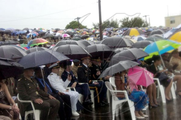 Norman Grindley/Chief Photographer HERE COMES THE RAIN AGAIN: The umbrellas came out during the Jamaica Defence Force's Change of Command parade on the polo field at Up Park Camp on Saturday.