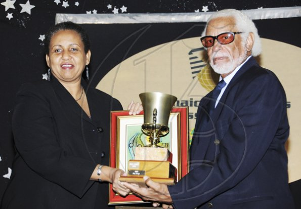 Winston Sill / Freelance Photographer Jamaica Exporters Association (JEA) Awards Banquet, held at the Wyndham Hotel on Wednesday  night June 29, 2011. Here Winston Stona (right) presents the Model Exporter Trophy to Greta Bogues (left), of J Wray and Nephew.
