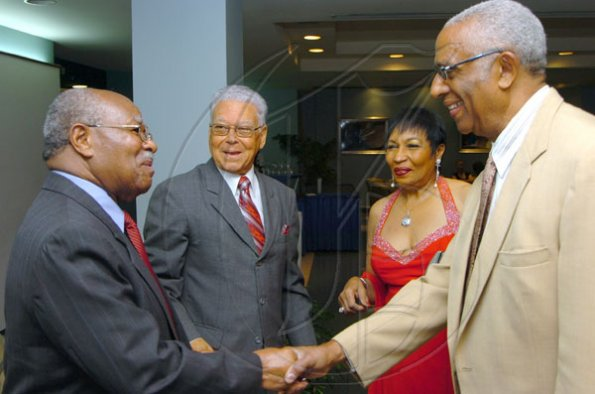 Rudolph Brown/Chief Photographer Garth Moodie, (right) and his wife Valrie greets by Lloyd Vermont, (left) and Oliver Jones Chairman of JMF at the Jamaica Medical Foundation awards and fund-raising banquet at the Hilton Hotel in New Kingston on Saturday, March 21-2009