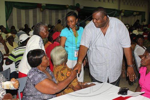 Anthony Minott/Freelance Photographer Mayor of Portmore Keith Hinds (standing), greets a senior citizen during Woody's Restaurant/Transjamaica Highway  sponsored Portmore Mayor's Senior Citizens Christmas treat at the Portmore HEART Academy on Wednesday, December 22, 2010. Over 200 Senior Citizens were feted. Other sponsors include Sovereign Supermarket, TDK tours, and YP Seaton.