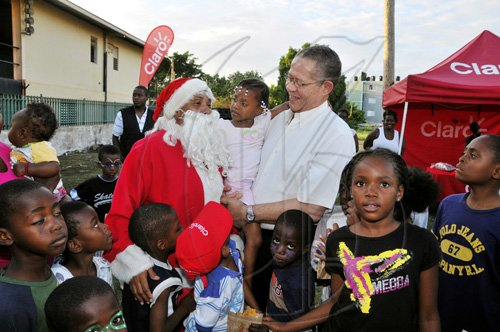 JIS Prime Minister Bruce Golding (right) and Santa share some  time with a young child at his annual West Kingston Christmas Treat at the Tivoli Gardens Community Centre in Kingston on Saturday, December 18, when  Mr Golding treated children and their parents at several locations including Tivoli, Fletcher's Land and Denham Town.