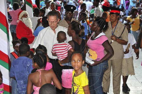 JIS Prime Minister, the Hon Bruce Golding, is the centre of attention at Saturday's Christmas Treat for children at the Tivoli Gardens community centre on Saturday, December 18. Children and parents were treated at several location locations in his West Kingston constituency, including Tivoli, Fletcher's Land and Denham Town.