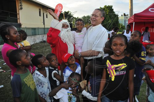 JIS Prime Minister, the Hon. Bruce Golding, shares some of his time with a young child and Santa Claus at his annual West Kingston Christmas Treat at the Tivoli Gardens Community Centre in Kingston on Saturday, December 18. Mr. Golding treated children and their parents at several locations including Tivoli, Fletcher's Land and Denham Town.