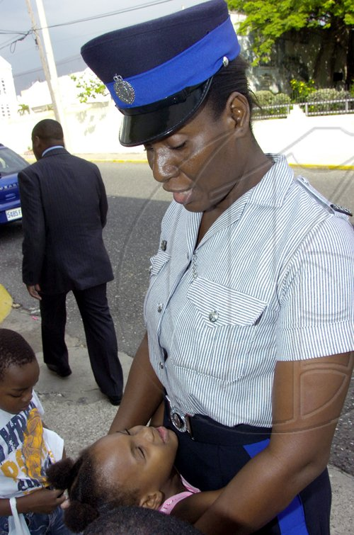 Norman Grindley/Chief Photographer Woman constable Donna Lindsay, assigned to to the house of parliament in Kingston find a new friend yesterday. The occasion was was a Christmas treat put on by staff at the House for children in the area.