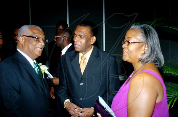 Winston Sill / Freelance Photographer Businessman Glen Christian (left), has the attention of his wife Marva and  W. Billy Heaven, president of the  Mico University Alumni Association (MOSA).  ******************************************************************* presents the Biennial Gold Medal Awards Banquet, held at the Jamaica Pegasus Hotel, New Kingston on Saturday night April 17, 2010.