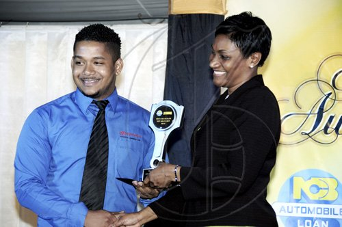 Winston Sill / Freelance Photographer Kevin Jackson of Toyota Jamaica takes the New Car Sales Representative 2009/2010. Here he is presented with it by Audrey Tugwell-Henry.  National Commercial Bank (NCB) Auto Dealers Awards Ceremony, held at Terra Nova All-Suite Hotel, Waterloo Road on Tuesday night April 5, 2011.