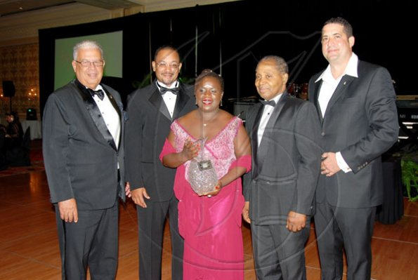 Photo by Sheena Gayle The Gleaner Company was presented with the Jamaica Committee Award of Excellence during Saturday's fund-raising Pineapple Ball event at the Ritz-Carlton Golf and Spa Resort in Montego Bay, St James. The Gleaner's award comes as the company is celebrating its 175th year in business. Representing the newspaper are board directors (from left): Winston Dear; Deputy Managing Director Christopher Barnes; Dr Carol Archer and Morin Seymour. Adam Shepard (right), of the Jamaica Committee, made the presentation.