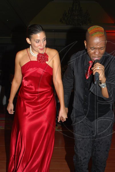 Janet Silvera Photo   Adrian Campbell of the group 'One Third' coerces Darcy Shepard to walk with him on the dancefloor during his performance to a large group of people who attended the Jamaica Committee Pineapple Ball at the Ritz Carlton Rose Hall last Saturday night.