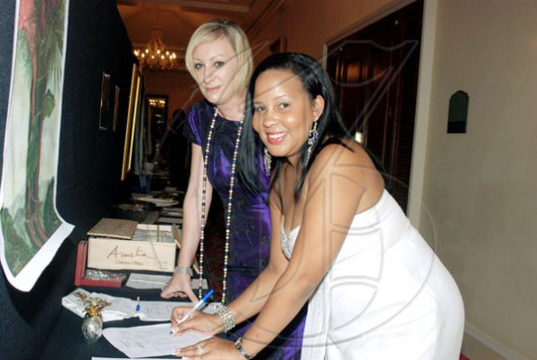 Janet Silvera Photo   Digicel's Shelly-Ann Curran and Antonia Graham checking out the silent auction at the Jamaica Committee Pineapple Ball at the Ritz Carlton Rose Hall in Montego Bay last Saturday night.