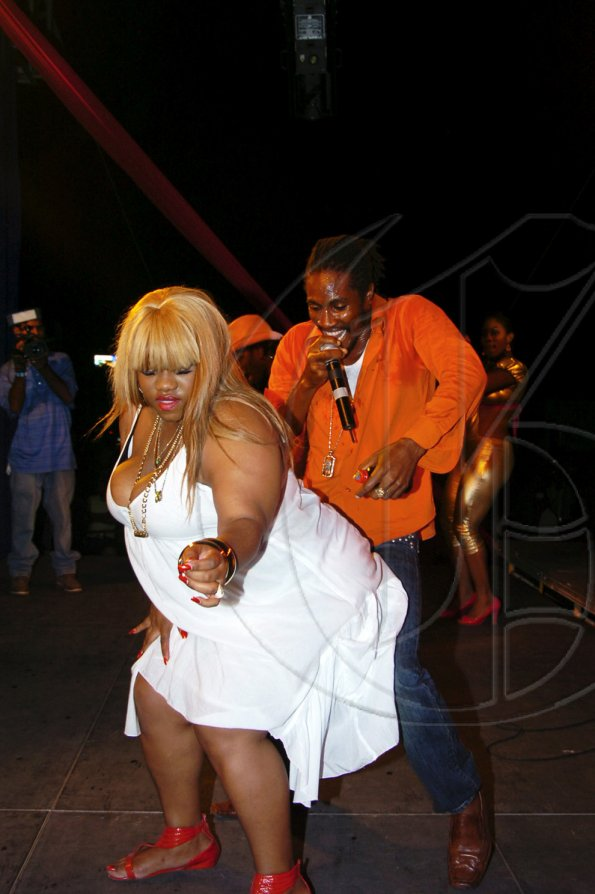 Publication: Daily Star Photo by Noel Thompson  Media personality 'Miss Kitty' getting down with Magnum Tonic Wine's King of Dance Hall, Singer Jah, at the Magnum Kings and Queen road show at Dump-up Beach in Montego Bay.