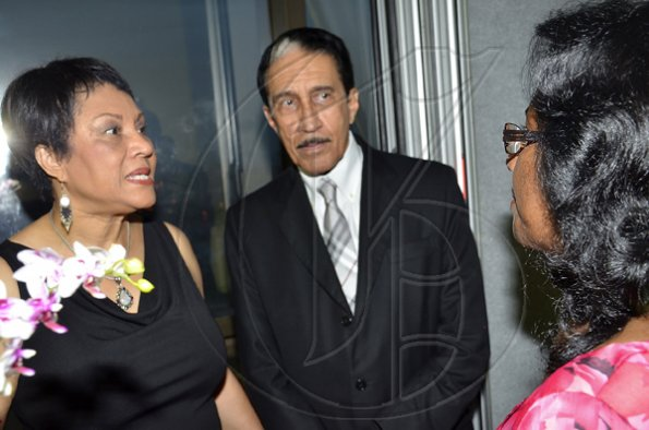 Rudolph Brown/Photographer Jackie McGregor (right), of the Rotary Club of Downtown Kingston, has the attention of past president Dr Robert Parchment and his wife, Patricia. The occasion was the Rotary Club of St Andrew North's 25th annual installation ceremony at the Wyndham Hotel in New Kingston on Monday, June 27, 2011.