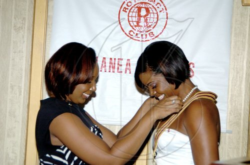 Winston Sill / Freelance Photographer  Tasha Wilson (left) hands over the presidency reigns to Yahneake Sterling.        Rotaract Club of Liguanea Plains, Installation and Awards Ceremony, held at Hotel Four Seasons, Ruthven Road on Friday night July 30, 2010.