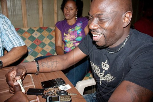 Now that's a winning smile! Marvin Lawrence takes no prisoners in his domino game at popular games night, 'Deuces Wild'.