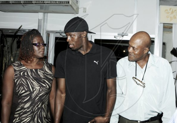 "Winston Sill / Freelance Photographer Jennifer Bolt, mother of Usain Bolt (centre), share a private moment with him and his dad  Wellesley Bolt.  ****************************************************************************,Launch and book signing of Usain Bolt book, ""My Story 9.58-- Being The World,s Fastest Man"", held at the Terra Nova All-Suite Hotel, Waterloo Road on Thursday night October 21, 2010. Here are Jennifer Bolt (left), mother; Bolt (centre); and Wellesley Bolt (right), father."
