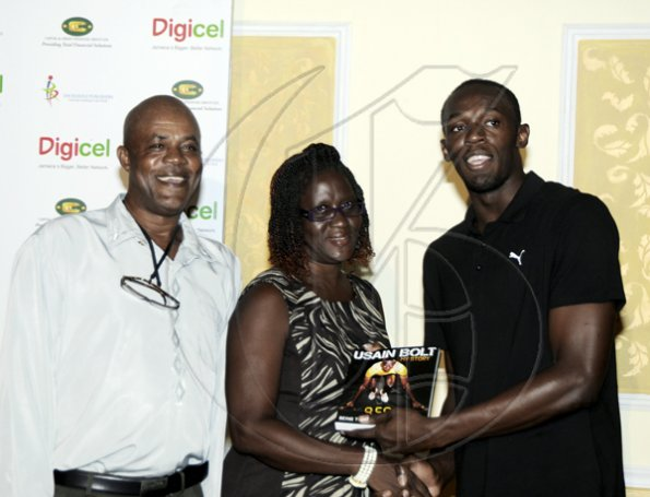 "Winston Sill / Freelance Photographer Launch and book signing of Usain Bolt book, ""My Story 9.58-- Being The World,s Fastest Man"", held at the Terra Nova All-Suite Hotel, Waterloo Road on Thursday night October 21, 2010. Here Bolt (right) presents a copy of his book to his mother Jennifer Bolt (centre), looking on at left is his dad Wellesley."