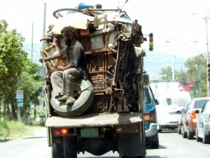 Men transporting a truck with scrap metal - File