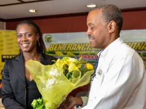 Olympian Merlene Ottey  being presented with flowers by  Chief Executive Officer of Grace Foods, Michael Ranglin, upon arriving at the Norman Manley International Airport in Kingston - JIS PHOTO